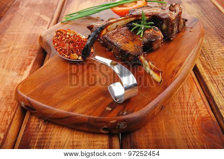 savory plate on wood : grilled ribs on plate with chives and tomato on wooden table