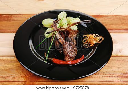 roast ribs on wooden table with grapes