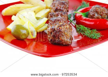 roast cutlets on red dish with peppers and potatoes