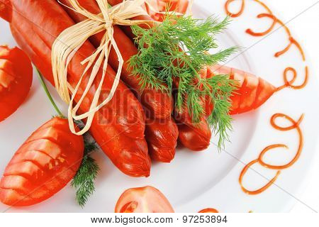 smoked sausages on a white plate over white