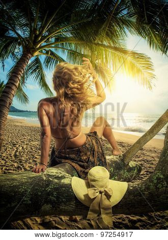 Woman in sarong on the beach at sunrise in Thailand