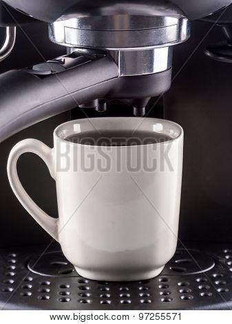 Closeup of modern coffee machine with white mug filled with hot coffee