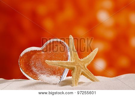 clear glass heart with starfish on white sand beach, and red glitter backdrop