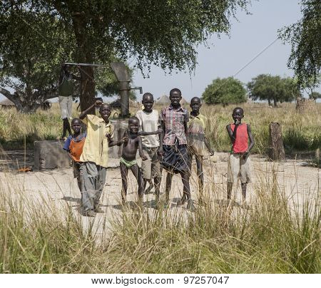 LILIIR, SOUTH SUDAN-DECEMBER 4, 2010: A group of boys stand in front of the village well in Liliir, South Sudan