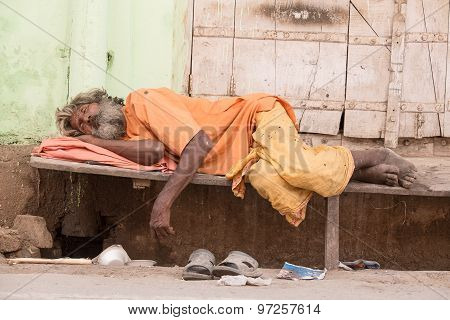 Indian Homeless Man Sleeps  Near The Ghat Along The Sacred Sarovar Lake