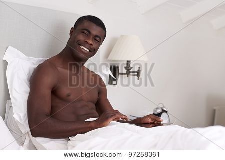 portrait of handsome african black man with tablet computer sitting comfortably in bed at home