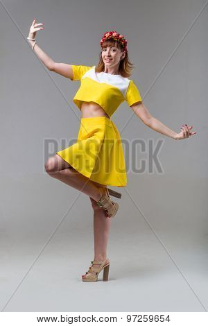 Woman in yellow dress with red wreath dancing on gray