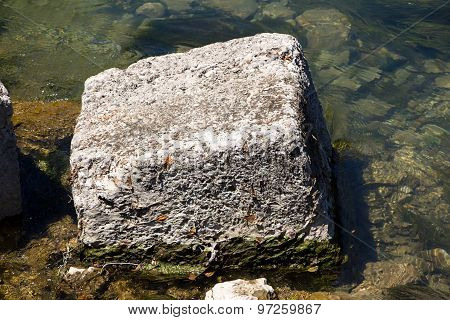 Photo of square stone among water