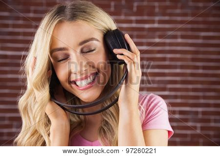 A beautiful woman enjoying listening her music against a red brick wall