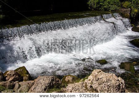 Photo of foaming flowing water among stones
