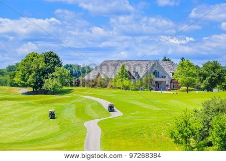 Golf place and custom built luxury big house on background.