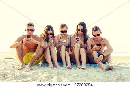 friendship, leisure, summer, technology and people concept - friends with smartphones sitting on sandy beach