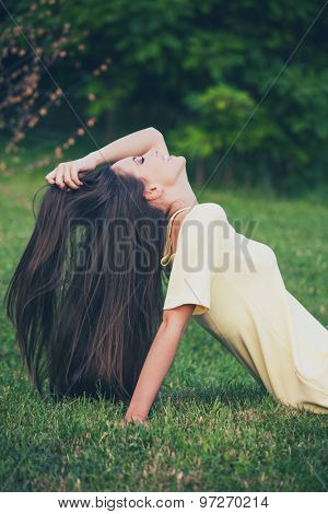 smiling girl with long healthy hair enjoy in nature, profile, sit in grass with hand in hair