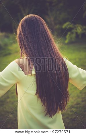 young woman with long straight hair, back shot, outdoor in park, retro colors