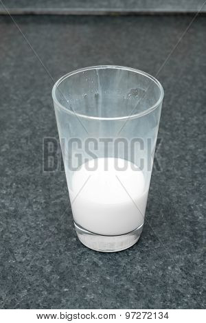 Unfinished glass of milk on the table. Dairy products