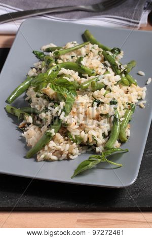 Risotto with green beans and basil leaves on a rectangular dish