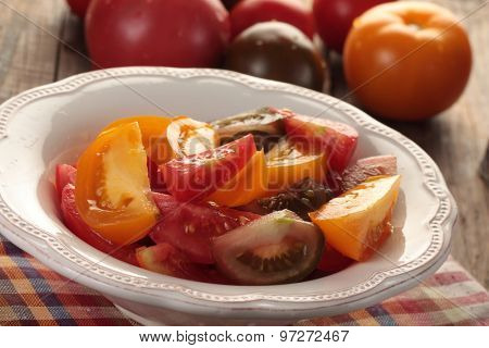 Sliced tomatoes in a bowl on a rustic table