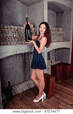 Beautiful Girl In The Wine Cellar Holds A Large Bottle Of Wine