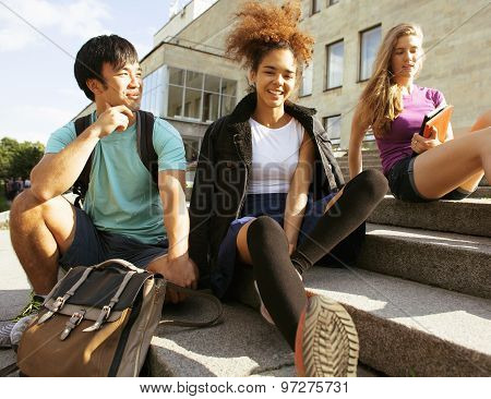 cute group of teenages at the building of university with books huggings, back to school