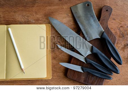 Set Of Kitchen Knifes On Wooden Cutting Board On Old Wooden Table