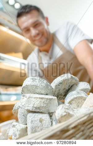 Cheese shop worker with new stock