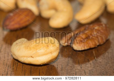 Assorted nuts on dark wooden table, focus on cashew