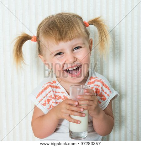 2-year-old girl  drink the milk on the floor in her home. close-up