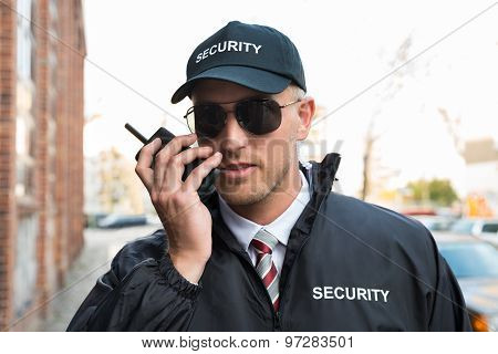 Security Guard Talking On Walkie-talkie