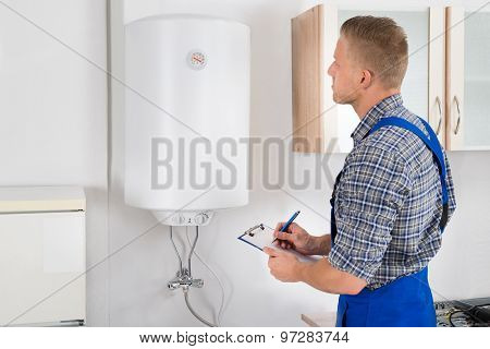 Man With Clipboard While Looking At Electric Boiler