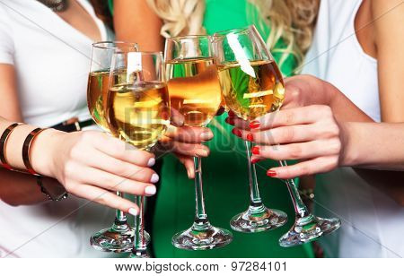 Group of partying girls clinking flutes with sparkling wine, close up