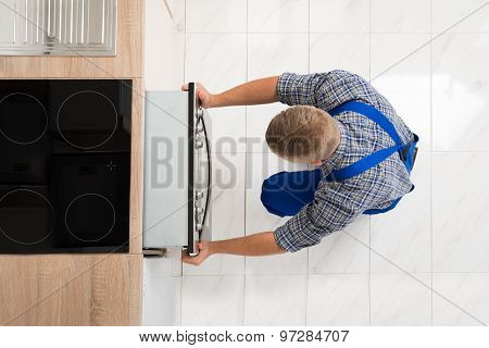 Man Repairing Kitchen Oven