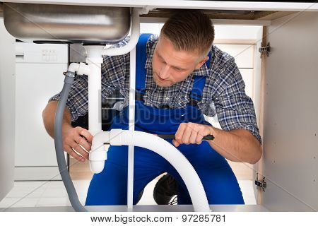 Plumber Fixing White Sink Pipe