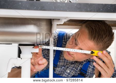 Plumber Measuring Sink Pipe