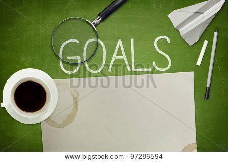 Goals concept on blackboard with empty paper sheet