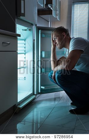 Man Looking For Food In Fridge