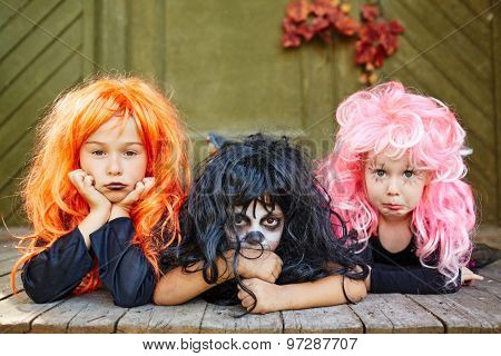 Group of cute girls in wigs looking at camera
