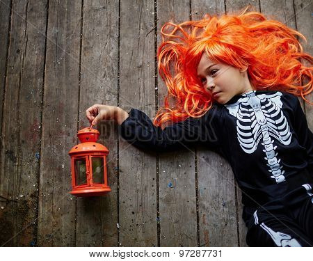 Relaxed girl in orange wig and Halloween attire lying on wooden floor