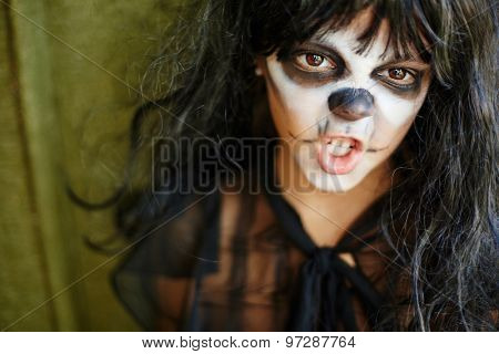 Furious witch with painted face looking at camera