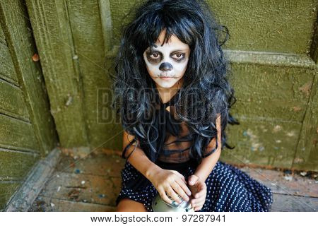 Sad girl with artificial hair sitting by wall of haunted house