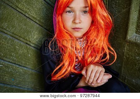 Calm little girl in orange wig looking at camera