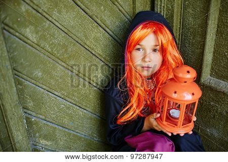 Little girl in orange wig and Halloween attire holding lantern