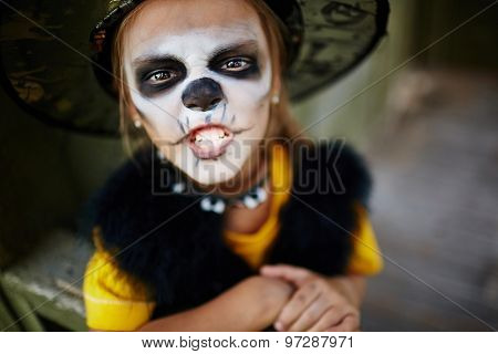 Halloween girl with painted face looking at camera