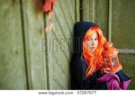 Little girl in Halloween attire holding lantern with candle