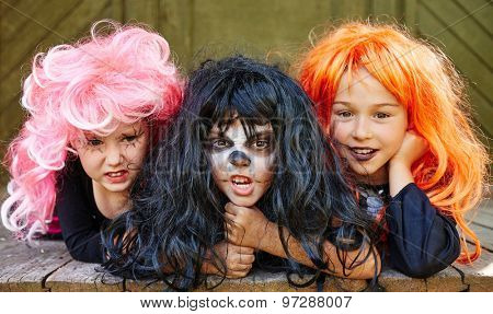 Small frightening witches in wigs looking at camera