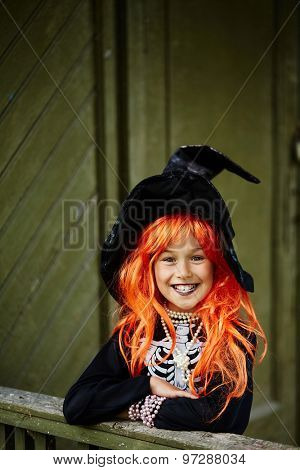 Halloween girl in black hat looking at camera