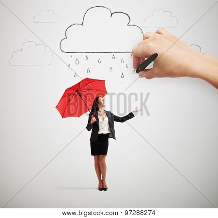 big hand drawing clouds with drops, smiley businesswoman with red umbrella standing under rain and looking up over light grey background
