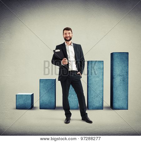 successful businessman with black folder smiling and looking at camera over blue concrete diagram