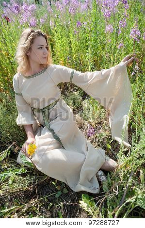 Beautiful sad girl sitting on meadow