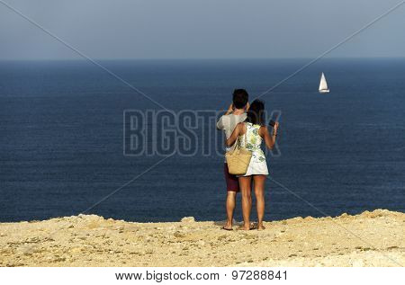 Beautiful young couple in love enjoying the ocean shore