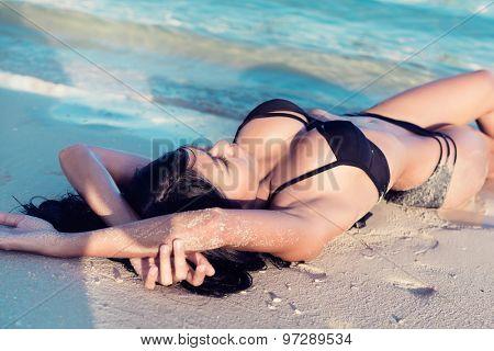 Beautiful girl or woman in water on sand beach